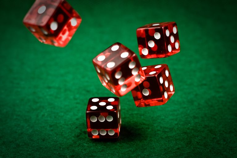 three red dices laying on the green poker table