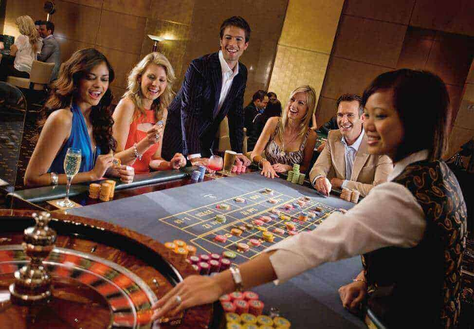 a group of people cheering while the dealer is spinning the roulette wheel