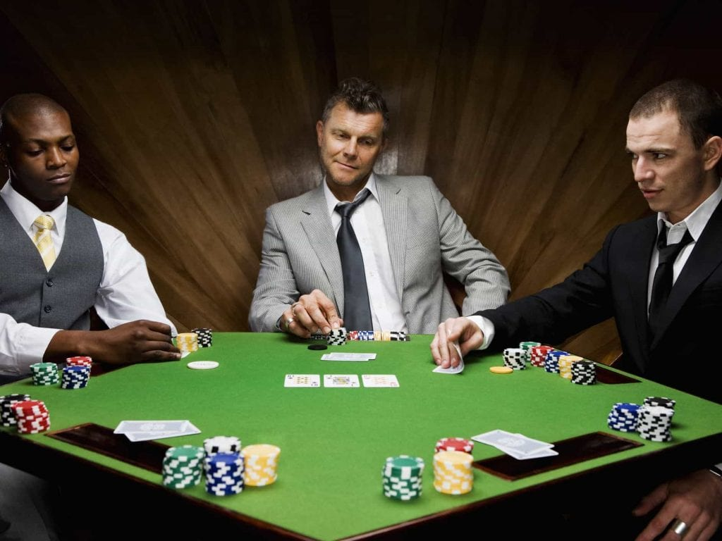 three men sitting on a poker table playing