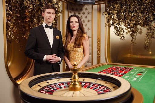 casino hosts standing next to roulette table