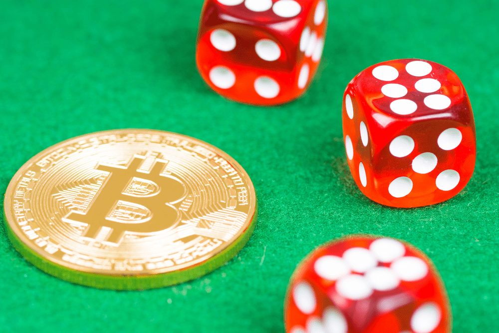 three red dices with a bitcoin monet on a green table