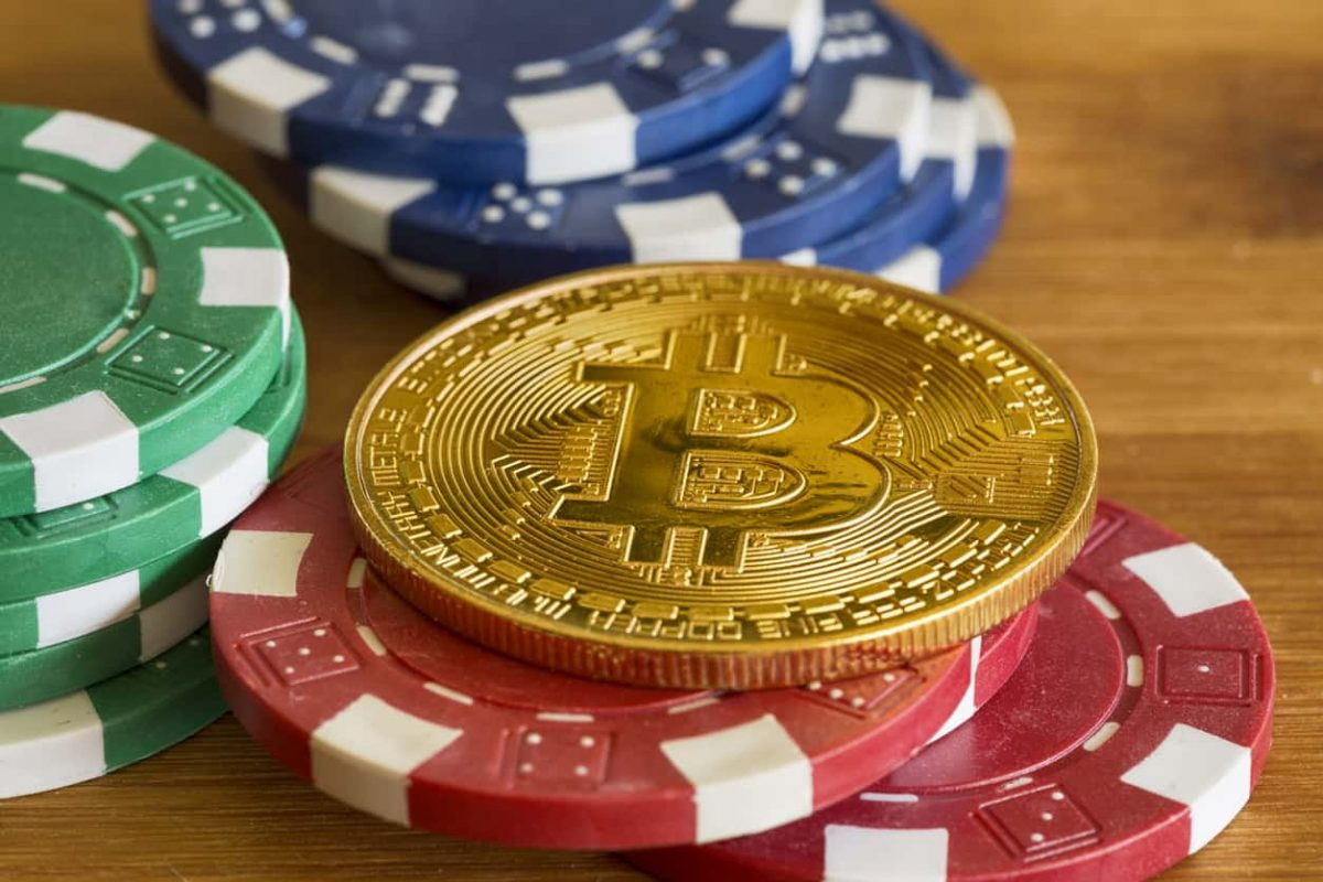 bitcoin with poker chips laying on a wood table