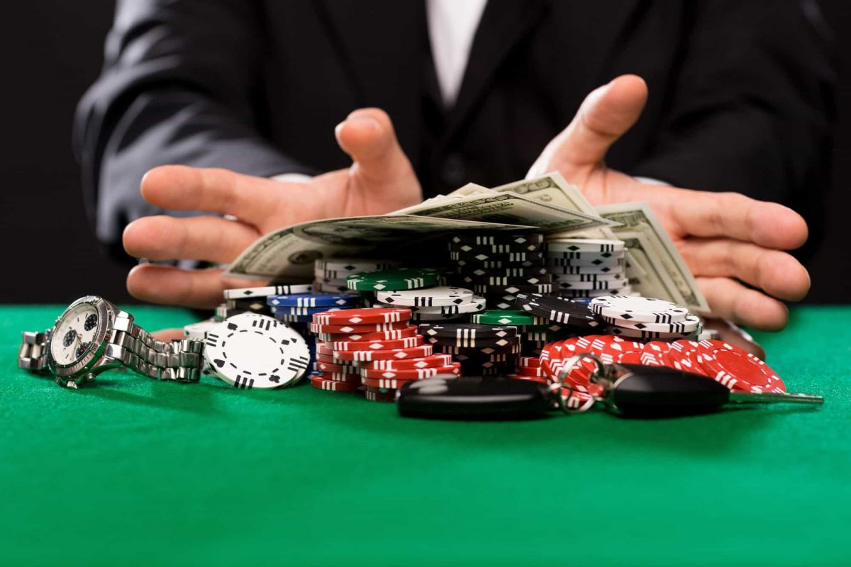 a man pushing casino chips and money on a poker table